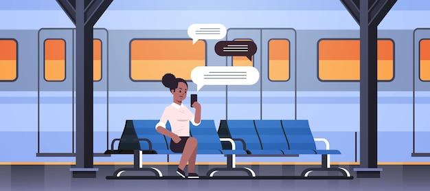 Frau sitzt auf plattform mit chat mobile app auf smartphone soziale netzwerk chat blase kommunikationskonzept zug u-bahn oder bahnhof in voller länge horizontale vektor-illustration
