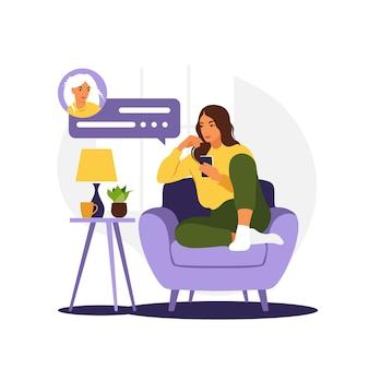 Frau sitzt auf sofa mit telefon. arbeiten im telefon.