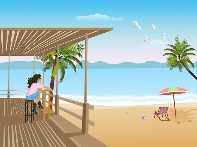 Frau sitzt in einem bambus-café an einem strand am meer mit meer und himmel im hintergrund.