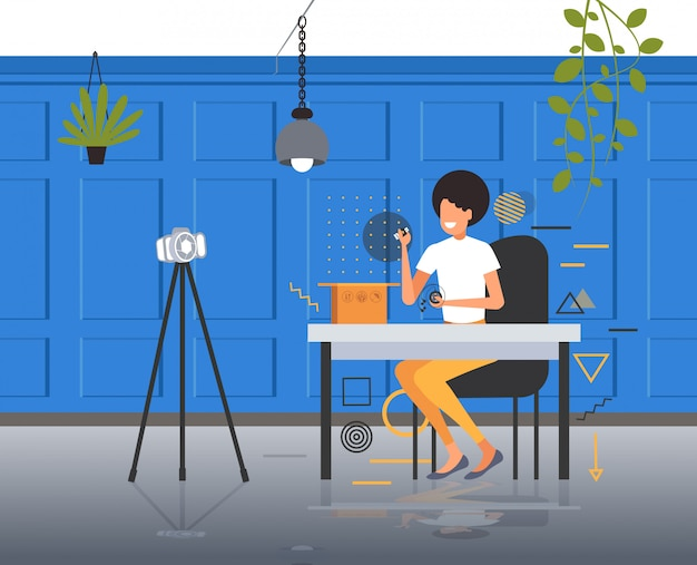 Frau technologie blogger eröffnungsbox mit kopfhörern aufnahme unboxing video mit kamera auf stativ blogging live-streaming-konzept moderne büro interieur horizontal in voller länge