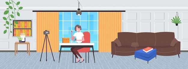 Frau technologie blogger öffnung box mit kopfhörern aufnahme unboxing video mit kamera auf stativ blogging live-streaming-konzept wohnzimmer innenraum horizontal in voller länge