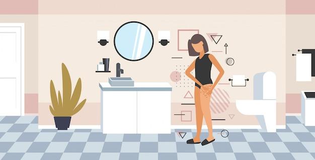 Frau testet hautpräsenz von dehnungsstreifen, die cellulite auf ihrem gesäßmädchen prüfen, das fettfalte auf hüftdiät-gewichtsverlustkonzept-badezimmerinnenraum in voller länge horizontal festklemmt