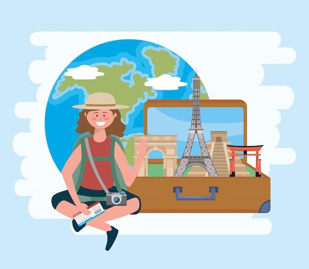 Frau trägt hut und sitzt mit rucksack und kamera