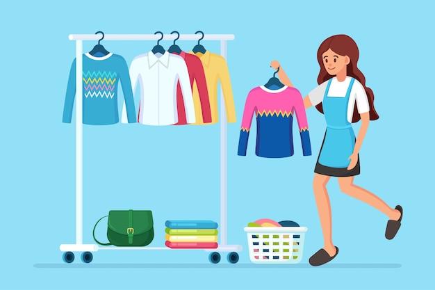 Frau wählt und probiert kleid an. mädchen in der nähe von kleiderschrank. metallregal mit kleidung, taschen auf kleiderbügeln in der boutique. ladenstand mit modischem outfit. innenraum der umkleidekabine.