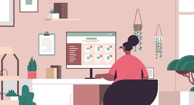 Frau wählt waren auf monitor bildschirm online-shopping cyber montag großen verkauf urlaub rabatte e-commerce-konzept wohnzimmer innenporträt