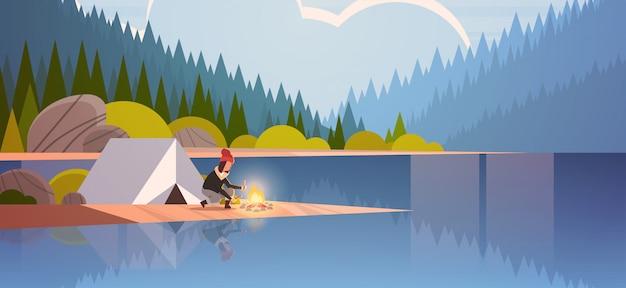 Frau wanderer machen feuer in der nähe von zeltlager mädchen halten brennholz für lagerfeuer wandern camping konzept landschaft natur fluss wald berge