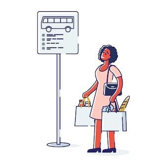 Frau wartet auf bus. afroamerikanerpassagier, der am straßenschild mit busfahrplan nahe straße steht