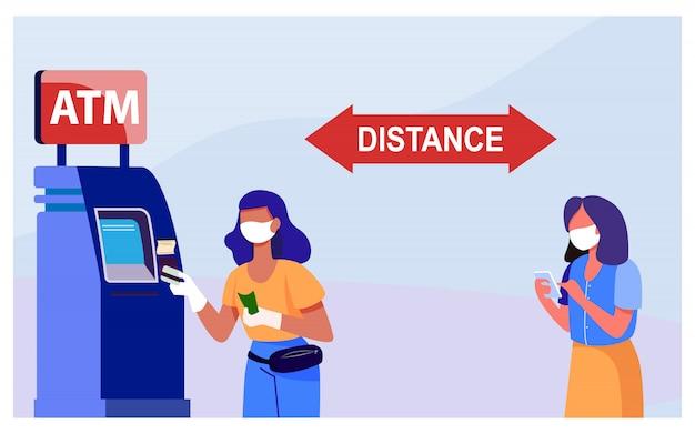 Frauen benutzen geldautomaten und halten abstand