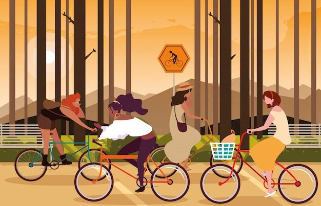 Frauen, die fahrrad in der waldlandschaft mit signage für radfahrer reiten