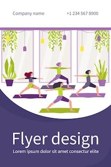 Frauen, die im fitnessclub trainieren, an der yoga-klasse teilnehmen und in der kriegerpose auf der matte stehen