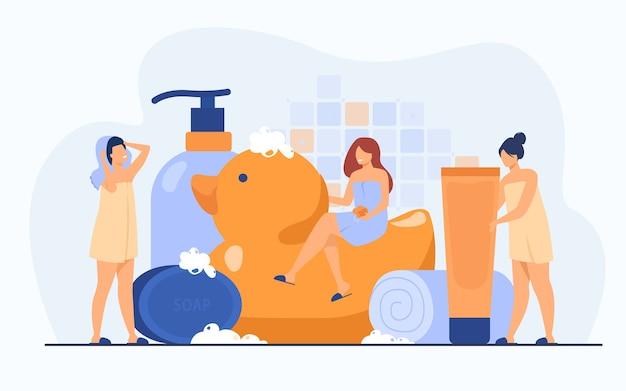 Frauen, die mit schwamm und seife in handtücher gewickelt sind, zwischen badzubehör, tuben und shampooflaschen. vektorillustration für badezimmer-, spa-, routine-, hygienekonzept