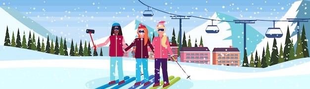 Frauen, die selfie an der skiorthotelfahne nehmen