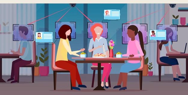 Frauen diskutieren das genießen des essens während des treffens besucheridentifikation gesichtserkennungskonzept überwachungskameraüberwachung cctv-system modernes restaurant cafe interieur horizontal in voller länge