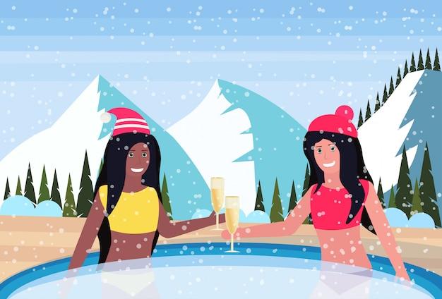 Frauen halten champagnergläser im thermischen jacuzzi im freien in den bergen