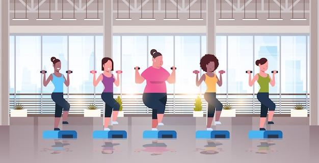 Frauen halten hanteln kniebeugen auf schritt plattform verschiedene körpertypen mädchen training im fitnessstudio