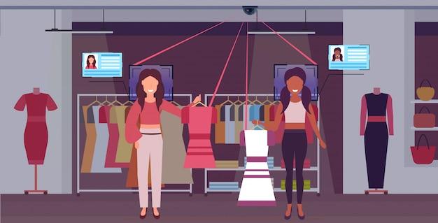 Frauen halten kleider kunden identifikation gesichtserkennung konzept überwachungskamera überwachung cctv-system mode boutique interieur in voller länge horizontal