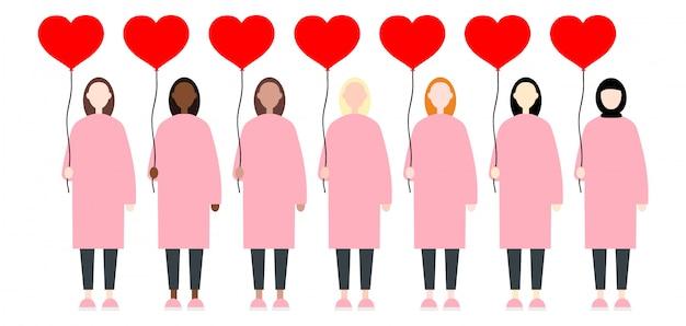 Frauen in der rosafarbenen kleidung, die rote ballonherzen hält