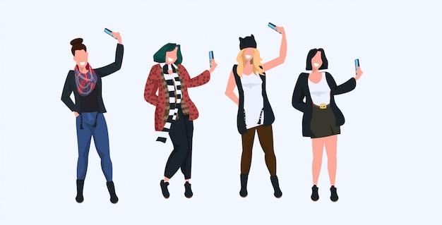 Frauen machen selfie-foto auf smartphone-kamera lässig weibliche zeichentrickfiguren fotografieren in verschiedenen posen weißen hintergrund in voller länge horizontal