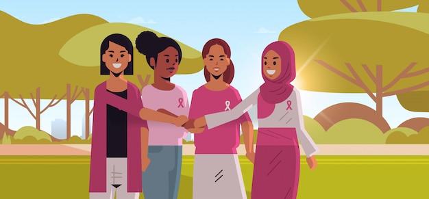 Frauen mit rosa bändern, die hände halten, mischen rassenmädchen, die zusammen brustkrebs-tageskrankheitsbewusstsein und -vorbeugungskonzept sommerpark-landschaftshintergrund flaches porträt horizontal stehen