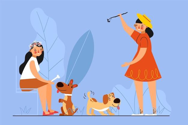 Frauen spielen zusammen mit ihren hunden