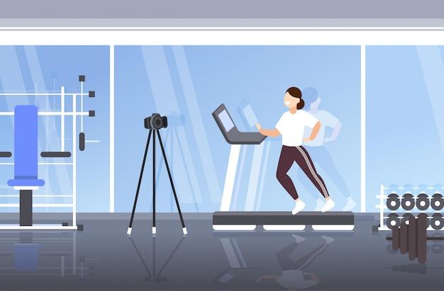 Frauenblogger, der auf tretmühlenaufnahmevideo mit kamera auf stativsozialem netz bloggt das moderne horizontale turnhalleninnere des gesunden lebensstilkonzeptes in voller länge läuft