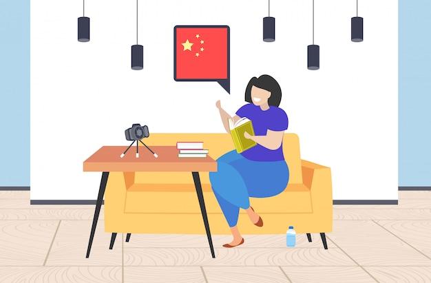 Frauenblogger, der wörterbuchvokabular-chatblase mit porzellanflaggenlehrer-aufnahmevideo mit kamera auf blogging konzept-wohnzimmerinnenraum des stativsozialmediennetzes horizontal hält