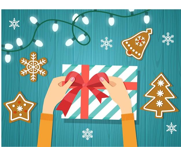Frauenhände geben verpacktes handgemachtes geschenk des weihnachtsfeiertags in papier mit rotem band. vektor-illustration.
