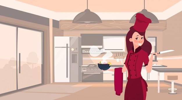 Frauenkoch, der dampfende schüssel mit suppe über modernem küchen-hintergrund hält