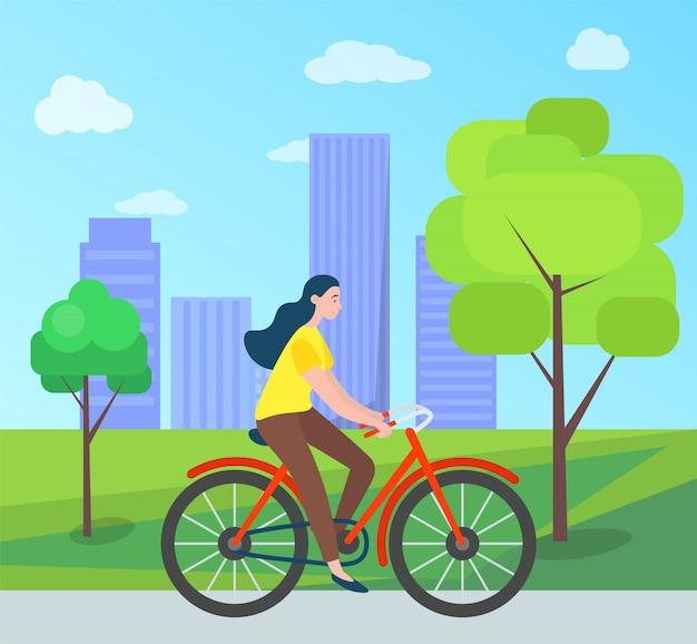 Frauenreiten auf fahrrad im grünen stadtpark, bäume