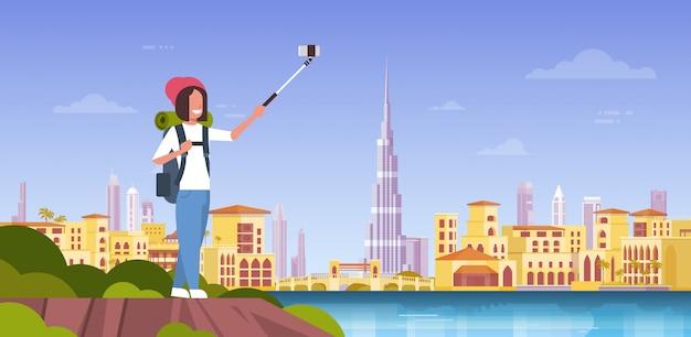 Frauentourist mit dem rucksack, der selfie-foto über schönem dubai-stadt-hintergrund macht