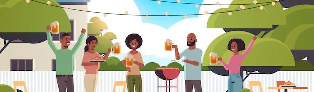 Freunde, die hot dogs auf grill vorbereiten und bier trinken glücklich afroamerikanische männer frauengruppe, die spaß hinterhofpicknick-grillpartykonzept flaches porträt horizontal hat