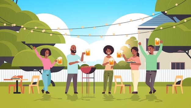 Freunde, die hot dogs auf grill vorbereiten und bier trinken glückliche afroamerikanische männerfrauengruppe, die spaß hinterhofpicknick-grillpartykonzept flach in voller länge horizontal hat