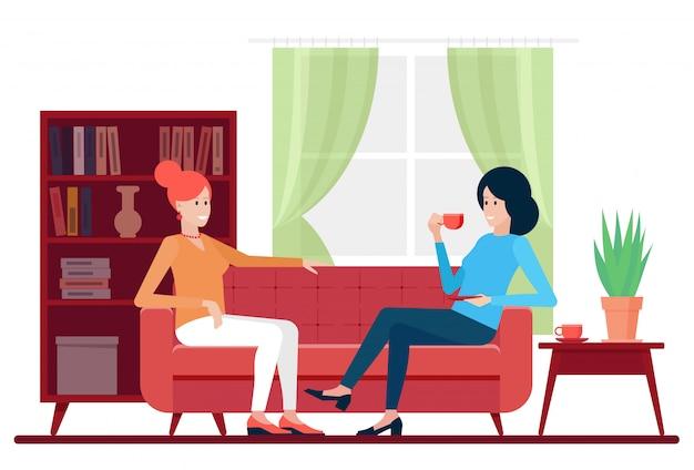 Freundinnen genießen heißes getränk und reden, während sie auf der couch zu hause entspannen.