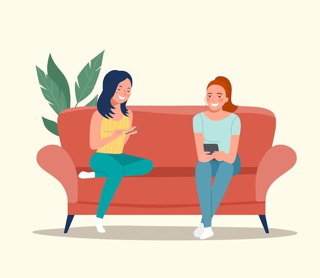 Freundinnen sitzen mit smartphones auf dem sofa