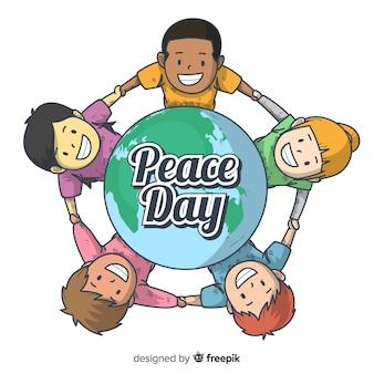 Friedenstageshintergrund mit den kindern, die hände um erde halten