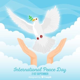 Friedenstageshintergrund mit der hand, die weiße taube freigibt