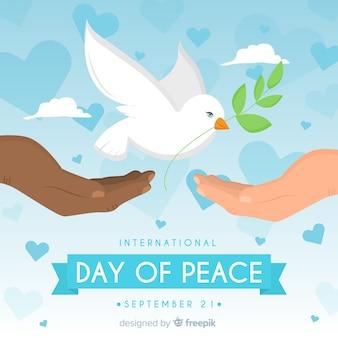 Friedenstageshintergrund mit weißer taube und den händen
