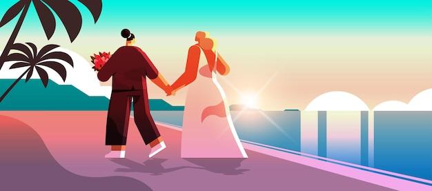Frisch verheiratetes lesbisches paar mit blumen am strand spazieren transgender-liebe lgbt-community-hochzeitsfeier