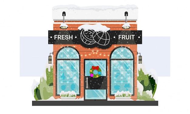 Frisches lebensmittelgeschäftschaufenster mit weihnachtskranz und girlanden und schnee lokalisiert auf weiß.