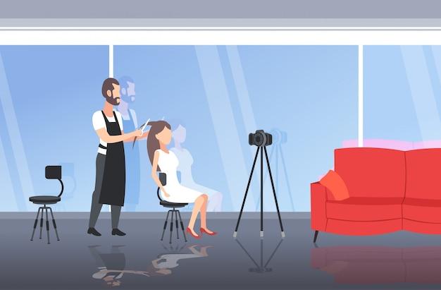 Friseur blogger machen frisur schneiden haarspitzen von frau kunden mann aufnahme online-video mit kamera auf stativ blogging-konzept modernen schönheitssalon interieur in voller länge horizontal