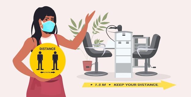 Friseur in maske mit gelbem schild, das abstand hält, um horizontales porträt des coronavirus-pandemie-schönheitssalons zu verhindern
