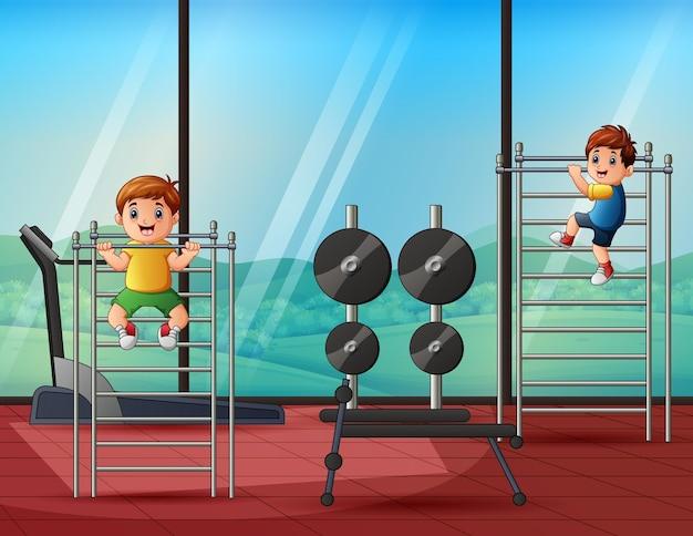 Fröhliche kleine jungs ziehen sich in einem fitnessstudio an einer horizontalen sportstange hoch