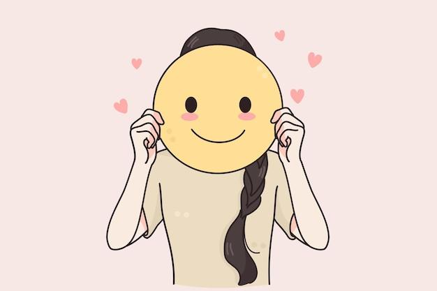 Fröhliche positive frau, die lächelndes emoticon steht und hält