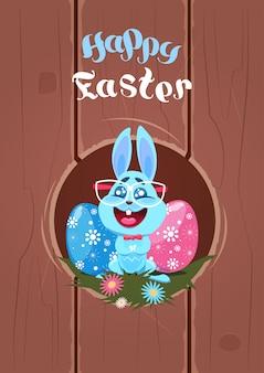 Frohe ostern dekor grußkarte mit lustigen bunny in gläsern und verzierten eiern urlaub dekoration hintergrund