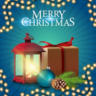 Frohe weihnachten, blaue quadratische grußpostkarte mit geschenk, vintage laterne, weihnachtsbaumast mit einem kegel und ein weihnachtsball