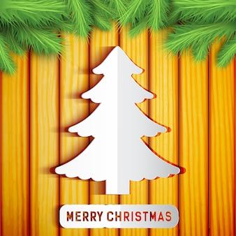 Frohe weihnachten dekorative schablone mit papierbaum tannenzweigen auf holz