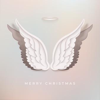Frohe weihnachten grußkarte. engelsflügel im geschichteten papierstil.
