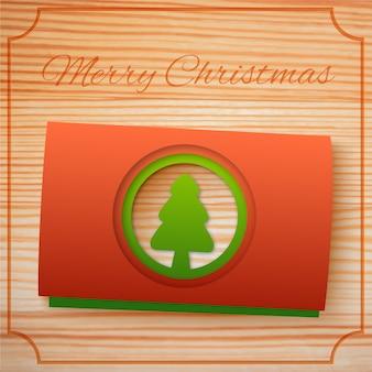 Frohe weihnachten grußschablone mit rotgrünen kartons tannenbaum auf holz