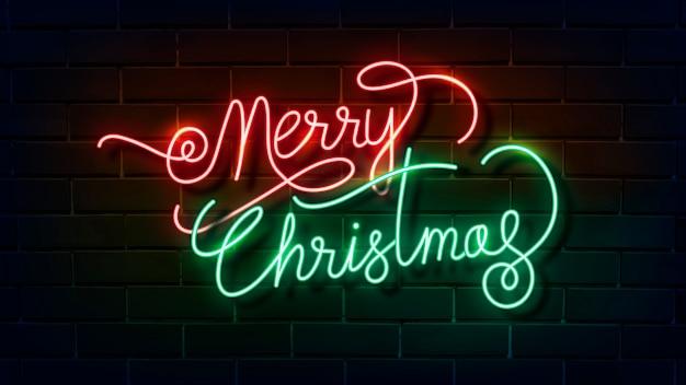 Frohe weihnachten leuchtreklame auf einer dunklen backsteinmauer