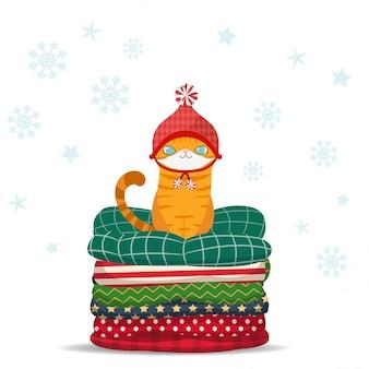 Frohe weihnachten, nette karikaturkatze, die auf stapel des kissens sitzt.